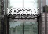 Het logo van Vescom draagt kenmerken van de tijd waarin het ontworpen werd (70er jaren): alsof het één dikke lijn uit een tube is. Dat maakt het vrij zwaar om op zo'n fijn gedetailleerde gevel te plaatsen. Om die reden is gekozen voor een contourlogo dat, ondanks een breedte van 3 meter, licht en transparant oogt. Borden zijn zwevend in portalen geplaatst.